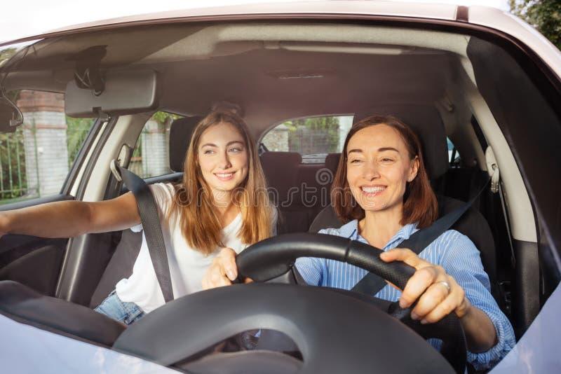 Οδήγηση μητέρων με την κόρη στο κάθισμα επιβατών στοκ εικόνες