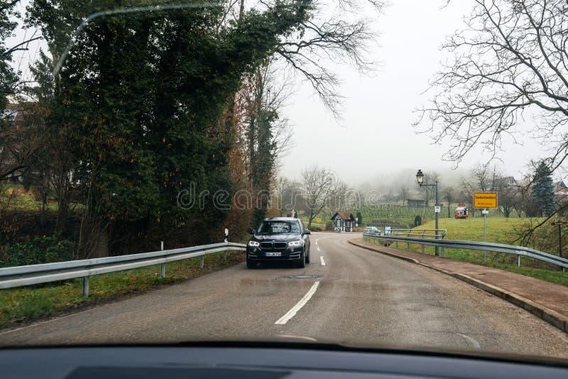Οδήγηση στην μπροστινή BMW SUV στο γερμανικό χωριό στοκ φωτογραφία