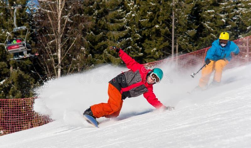 Οδήγηση Snowboarder στα βουνά σε μια ηλιόλουστη χειμερινή ημέρα στοκ εικόνα