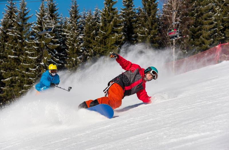 Οδήγηση Snowboarder στα βουνά σε μια ηλιόλουστη χειμερινή ημέρα στοκ εικόνες