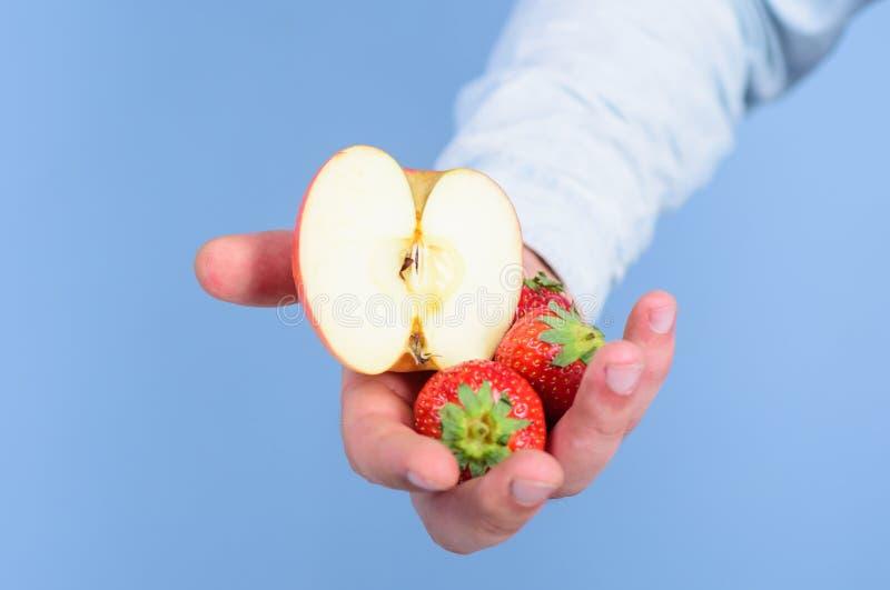 Οδηγίες οι ίδιοι Το χέρι προτείνει παίρνει τα φρούτα φραουλών και μήλων Τα φρούτα οργανικά μεταχειρίζονται ή τσιμπάνε Φρέσκια συγ στοκ φωτογραφία