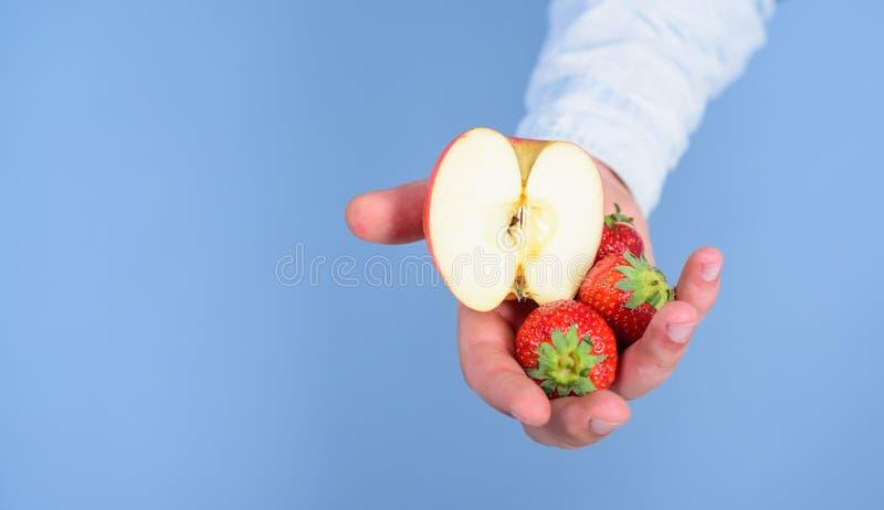 Οδηγίες οι ίδιοι Το χέρι προτείνει παίρνει τα φρούτα φραουλών και μήλων Αρσενικό χέρι με τις φράουλες και το μισό από το μπλε μήλ στοκ φωτογραφίες με δικαίωμα ελεύθερης χρήσης