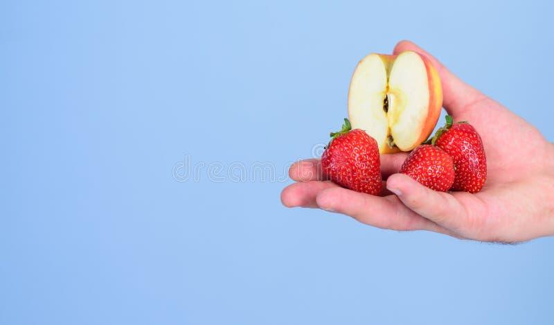 Οδηγίες οι ίδιοι Φρέσκια συγκομιδή των ώριμων μούρων φρούτων Το χέρι προτείνει παίρνει τα φρούτα φραουλών και μήλων Αρσενικό χέρι στοκ φωτογραφίες