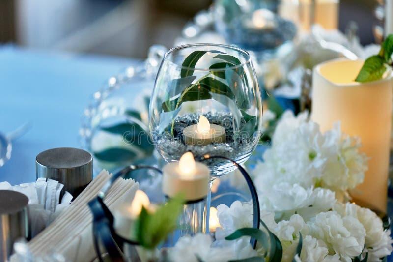 Οδηγημένα κεριά που καίνε μέσα διαφανές goblet γυαλιού Μπλε γάμμα στο σχέδιο στοκ φωτογραφίες