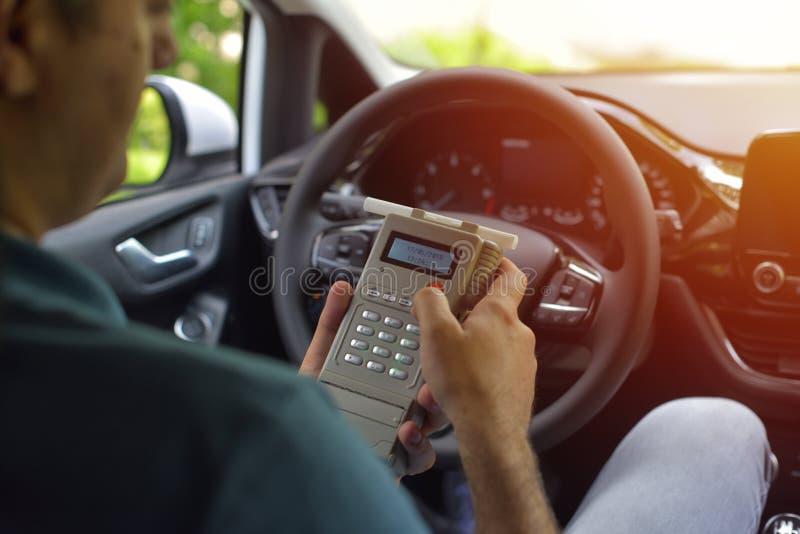 Οδηγός λόγω να υπόκειται στη δοκιμή για την περιεκτικότητα σε οινόπνευμα με τη χρήση του breathalyzer στοκ εικόνες