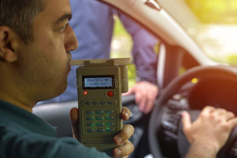 Οδηγός λόγω να υπόκειται στη δοκιμή για την περιεκτικότητα σε οινόπνευμα με τη χρήση του breathalyzer στοκ φωτογραφίες με δικαίωμα ελεύθερης χρήσης