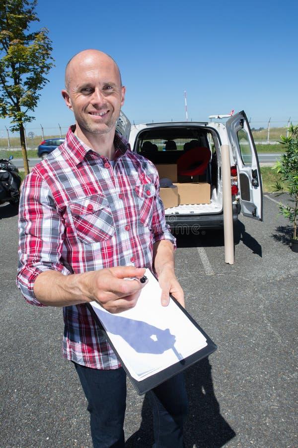 Οδηγός παράδοσης που χαμογελά στη κάμερα δίπλα στο φορτηγό στοκ φωτογραφία με δικαίωμα ελεύθερης χρήσης