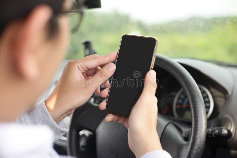 Οδηγός που ελέγχει το τηλέφωνό του στοκ εικόνα