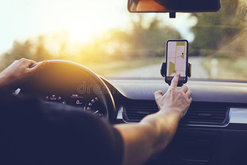 Οδηγός που χρησιμοποιεί τη ναυσιπλοΐα ΠΣΤ στο κινητό τηλέφωνο οδηγώντας το αυτοκίνητο στοκ φωτογραφίες με δικαίωμα ελεύθερης χρήσης