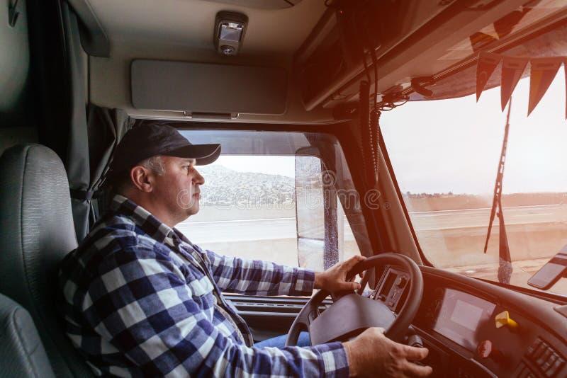 Οδηγός στην καμπίνα του μεγάλου σύγχρονου φορτηγού στοκ εικόνες