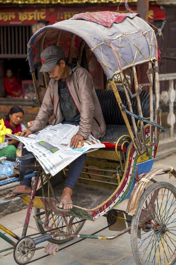 Οδηγός Rickshaw διαβάζει εφημερίδα στο Κατμαντού στοκ εικόνα