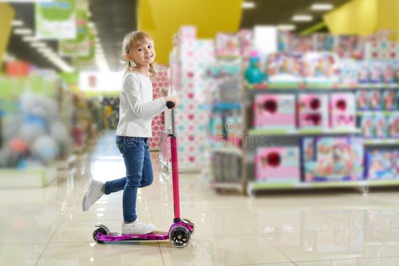 Οδηγώντας μηχανικό δίκυκλο παιδιών στο μεγάλο κατάστημα με τα παιχνίδια στοκ εικόνες