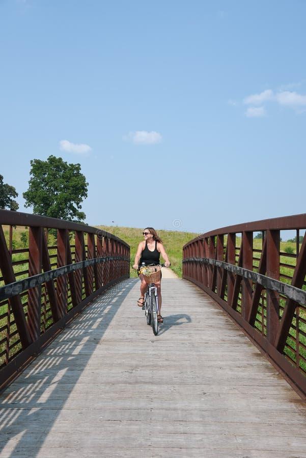 Οδηγώντας ποδήλατο γυναικών πέρα από τη γέφυρα στην πορεία ποδηλάτων στοκ φωτογραφίες με δικαίωμα ελεύθερης χρήσης