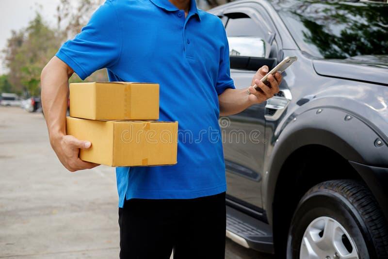 Οδηγώντας φορτηγό οδηγών παράδοσης με τα δέματα στο κάθισμα έξω από το warehou στοκ εικόνα