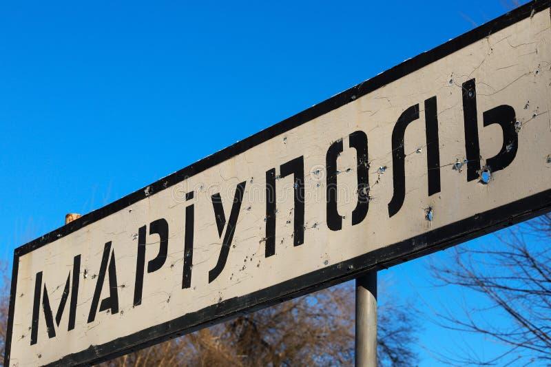 Οδικό σημάδι της ουκρανικής πόλης Mariupol, περιοχή του Ntone'tsk, που τρυπιέται με διατρητική μηχανή από τις σφαίρες κατά τη διά στοκ εικόνα