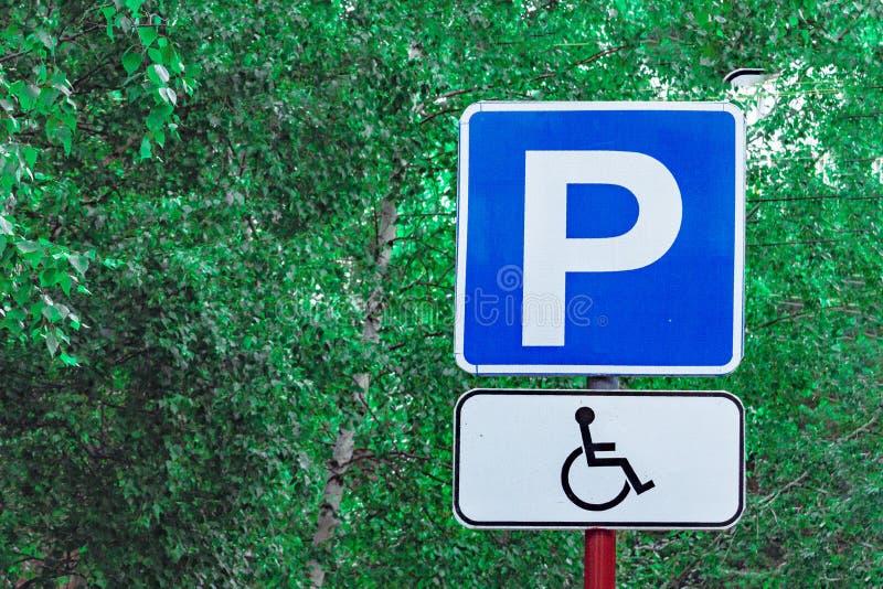 """Οδικό σημάδι """"άτομα με ειδικές ανάγκες που σταθμεύει """"σε ένα υπόβαθρο των πράσινων δέντρων, μπροστινή άποψη στοκ φωτογραφία με δικαίωμα ελεύθερης χρήσης"""