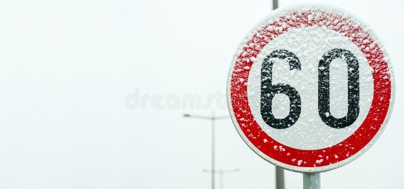 Οδικό όριο ταχύτητας 60 κυκλοφορίας σημάδι στην οδό που καλύπτεται με το χιόνι στενό σε επάνω χειμερινής εποχής κινδύνου ολισθηρό στοκ φωτογραφία