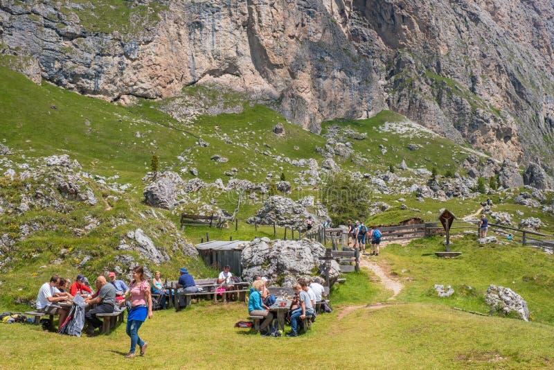 Οδοιπόροι βουνών που στηρίζονται και που τρώνε σε ένα λιβάδι βουνών στοκ εικόνες