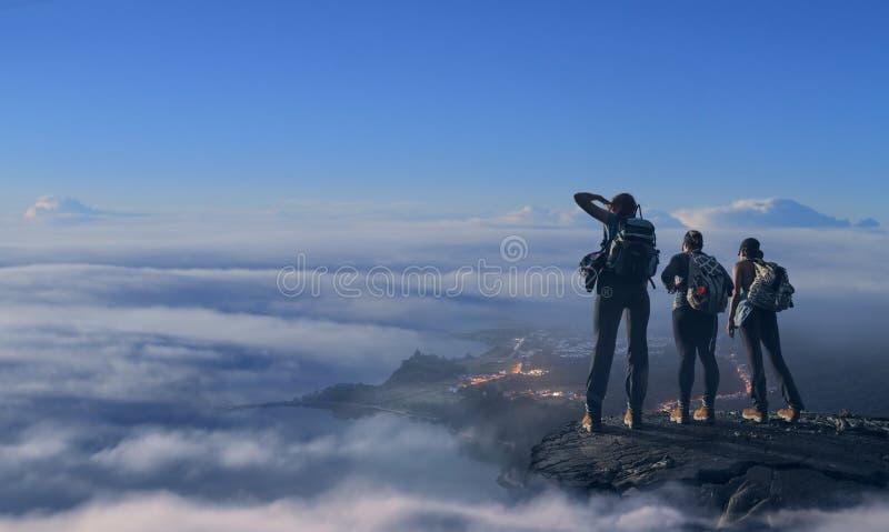Οδοιπόροι που στέκονται και που προσέχουν για τα σύννεφα στοκ εικόνα