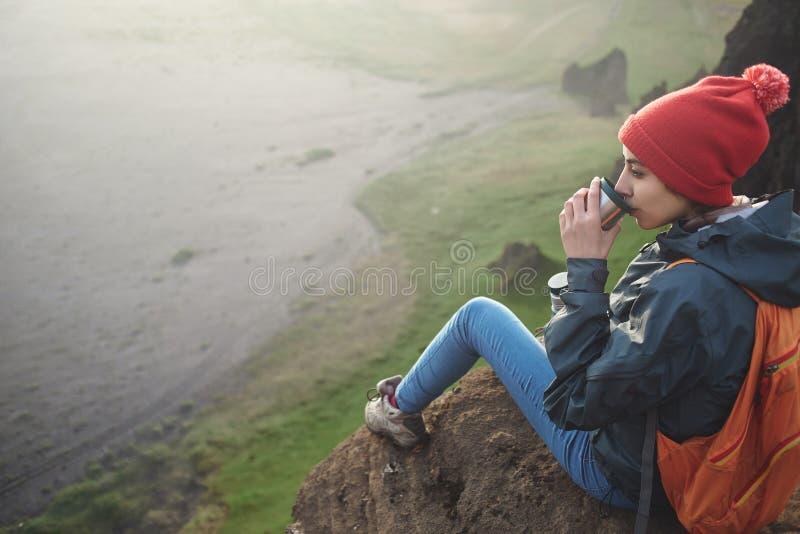 Οδοιπόρος γυναικών με το σακίδιο πλάτης που εγκαθιστά πάνω από ένα βουνό και που απολαμβάνει το ηλιοβασίλεμα στην Ισλανδία στοκ φωτογραφία με δικαίωμα ελεύθερης χρήσης