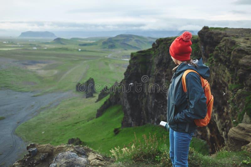 Οδοιπόρος γυναικών με το σακίδιο πλάτης που εγκαθιστά πάνω από ένα βουνό και που απολαμβάνει το ηλιοβασίλεμα στην Ισλανδία στοκ φωτογραφίες