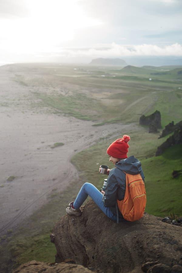 Οδοιπόρος γυναικών με το σακίδιο πλάτης που εγκαθιστά πάνω από ένα βουνό και που απολαμβάνει το ηλιοβασίλεμα στην Ισλανδία στοκ εικόνες