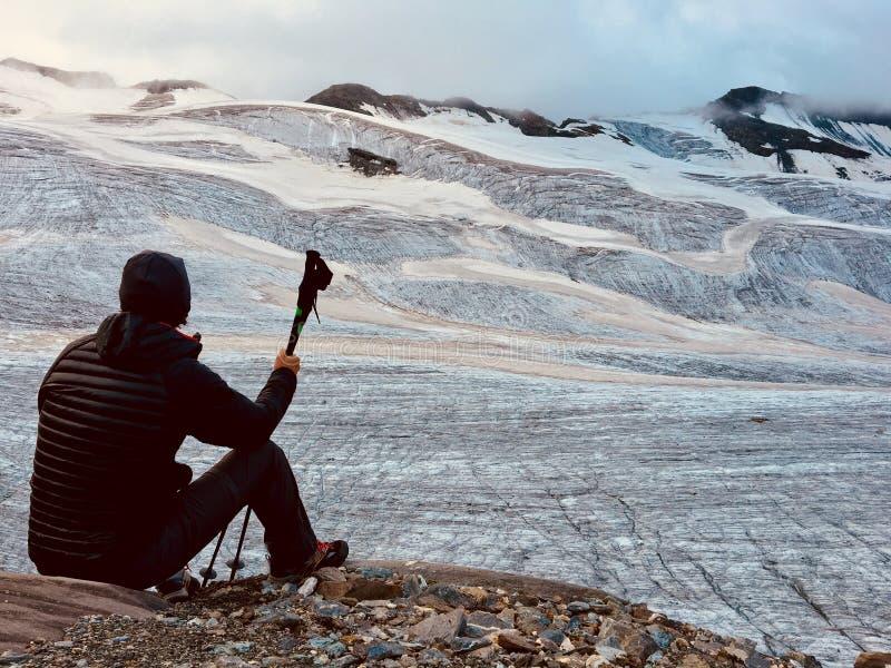 Οδοιπόρος μπροστά από έναν μεγάλο αλπικό παγετώνα υποστηρίξτε την όψη Ιταλικό όρος στοκ εικόνα