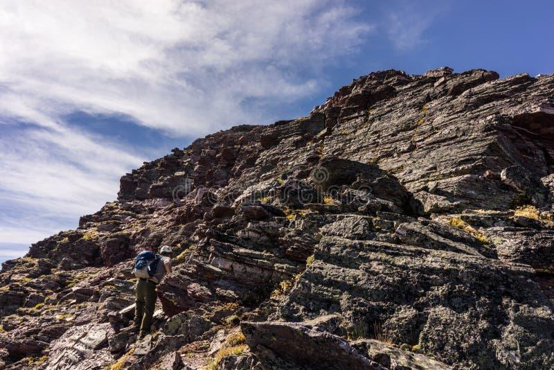 Οδοιπόρος στο εθνικό πάρκο παγετώνων, Μοντάνα Λήφθείτε σε μια ανάβαση της ΑΜ Siyeh στοκ εικόνες