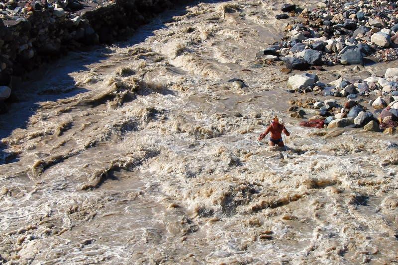 Οδοιπόρος wade ένας πολύ τραχύς ποταμός βουνών στοκ εικόνες