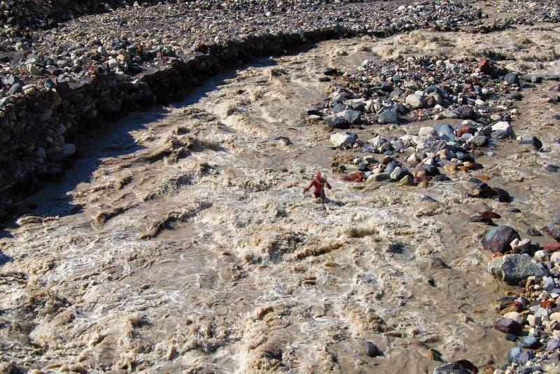 Οδοιπόρος wade ένας πολύ τραχύς ποταμός βουνών στοκ εικόνα