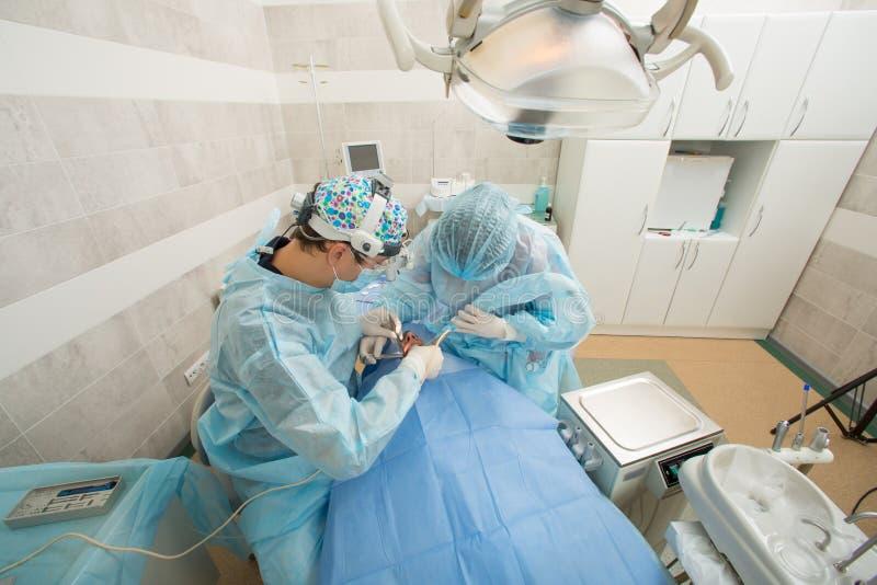 Οδοντίατροι με έναν ασθενή και έναν βοηθό κατά τη διάρκεια μιας οδοντικής επέμβασης Έννοια οδοντιάτρων Οδοντική χειρουργική επέμβ στοκ φωτογραφία με δικαίωμα ελεύθερης χρήσης