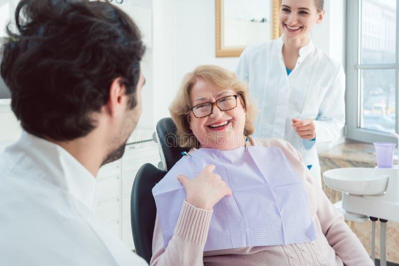 Οδοντίατρος και βοηθός που χαιρετούν τον ανώτερο ασθενή στοκ φωτογραφίες