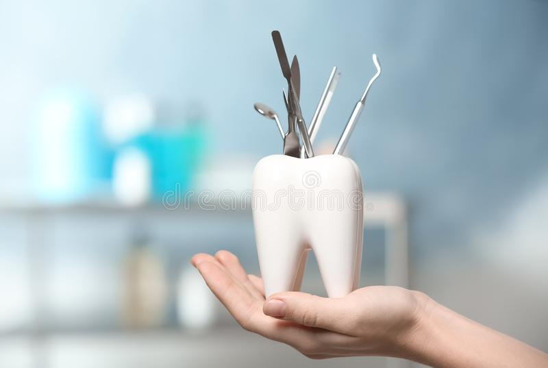 Οδοντίατρος με διαμορφωμένο το δόντι σύνολο κατόχων των επαγγελματικών εργαλείων στην κλινική στοκ φωτογραφία με δικαίωμα ελεύθερης χρήσης