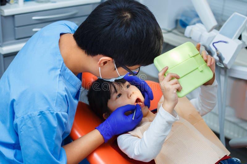 Οδοντίατρος που επιδεικνύει πώς να καθαρίσει τα δόντια στο μικρό ασθενή του που χρησιμοποιεί το α στοκ εικόνες