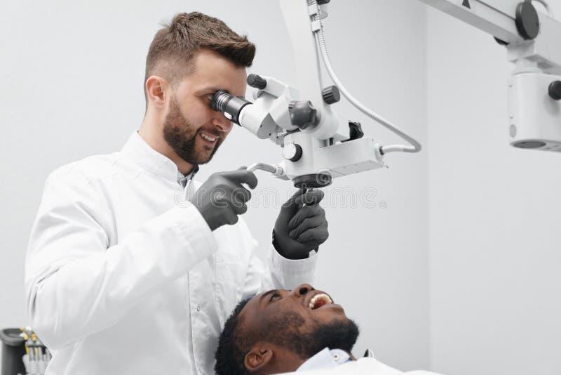 Οδοντίατρος που εργάζεται ενώ ασθενής που βρίσκεται στην καρέκλα με το ανοικτό στόμα στοκ εικόνα με δικαίωμα ελεύθερης χρήσης