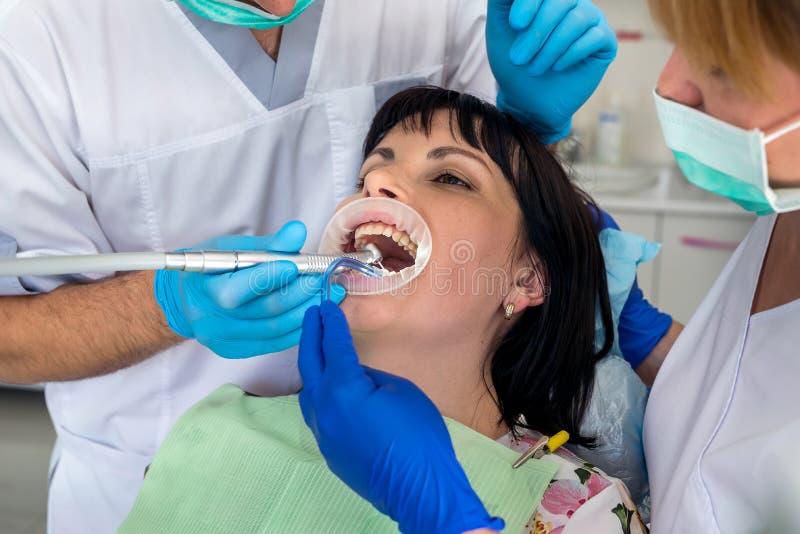 Οδοντίατρος που συνεργάζεται με τον ασθενή στην καρέκλα, οδοντιατρική στοκ εικόνα με δικαίωμα ελεύθερης χρήσης