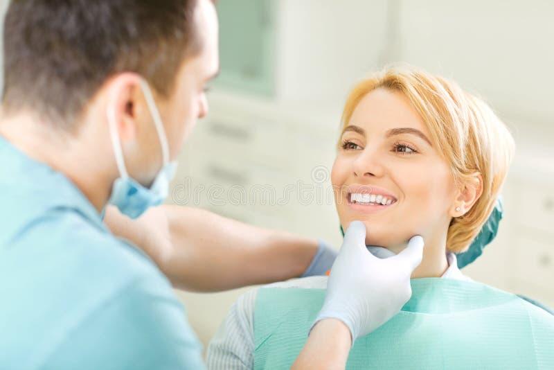 Οδοντίατρος που φαίνεται τα δόντια του υπομονετικού κοριτσιού στοκ φωτογραφία