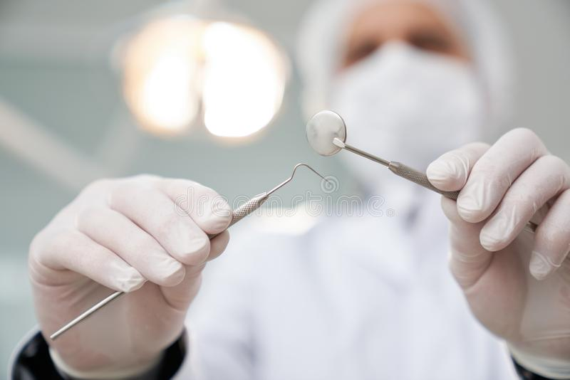 Οδοντίατρος στην ιατρική ΚΑΠ και μάσκα που εξετάζει τον ασθενή στοκ φωτογραφία