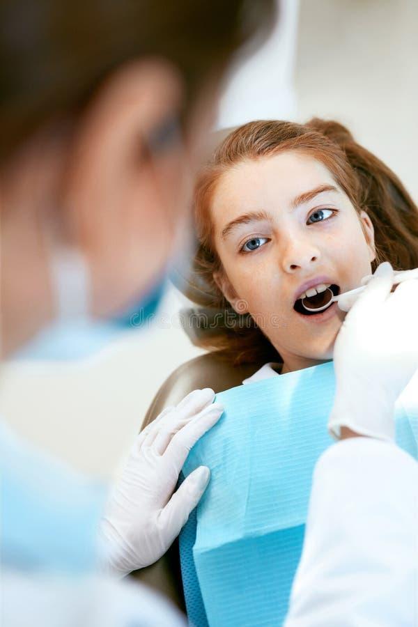 Οδοντική προσοχή Κορίτσι κατά τη διάρκεια της οδοντικής επεξεργασίας στην κλινική οδοντιατρικής στοκ φωτογραφίες
