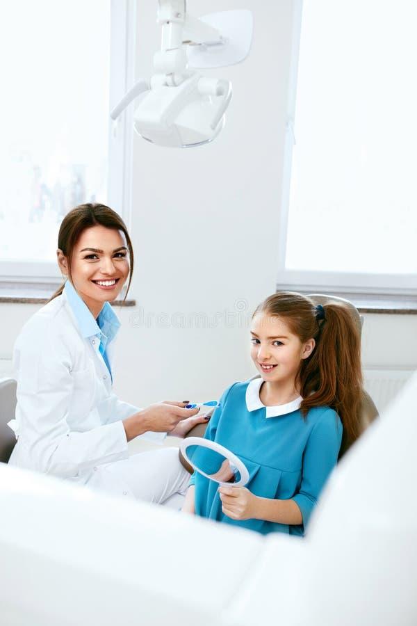 οδοντική υγεία Οδοντίατρος και ευτυχές κορίτσι στο γραφείο οδοντιατρικής στοκ εικόνες