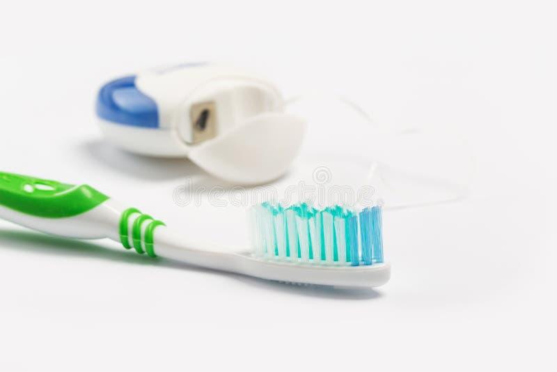 Οδοντικό νήμα και οδοντόβουρτσα που απομονώνονται σε ένα άσπρο υπόβαθ στοκ φωτογραφίες