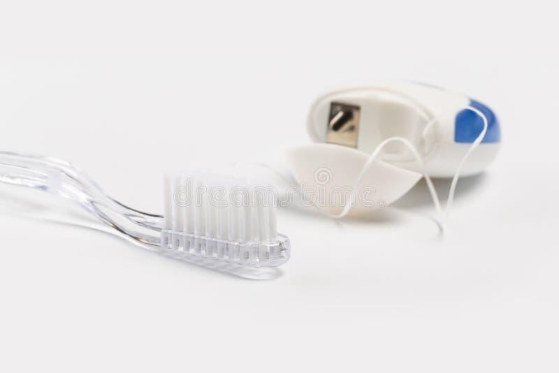 Οδοντικό νήμα και οδοντόβουρτσα που απομονώνονται σε ένα άσπρο υπόβαθρο στοκ εικόνα