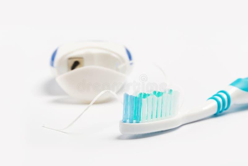 Οδοντικό νήμα και οδοντόβουρτσα που απομονώνονται σε ένα άσπρο υπόβαθρο στοκ εικόνες με δικαίωμα ελεύθερης χρήσης