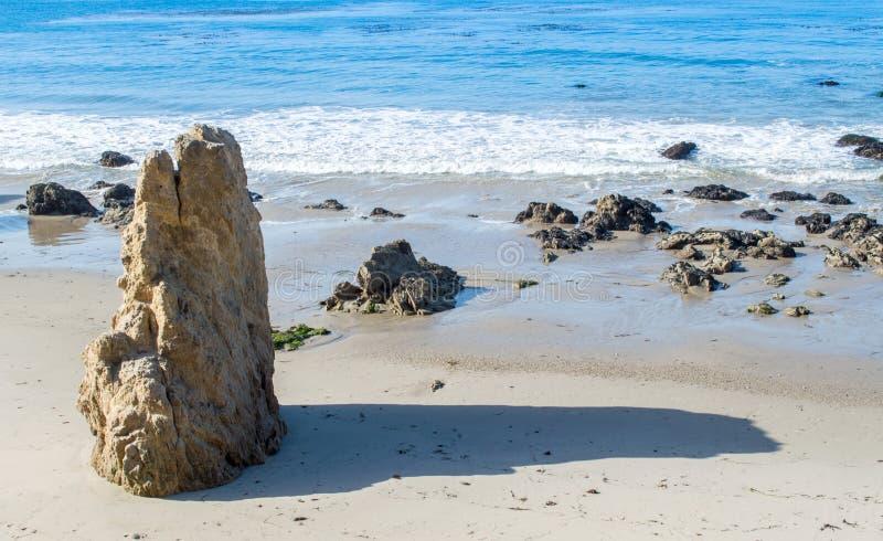 Οδοντωτός σχηματισμός βράχου σε μια αμμώδη παραλία στον ωκεανό στοκ εικόνα