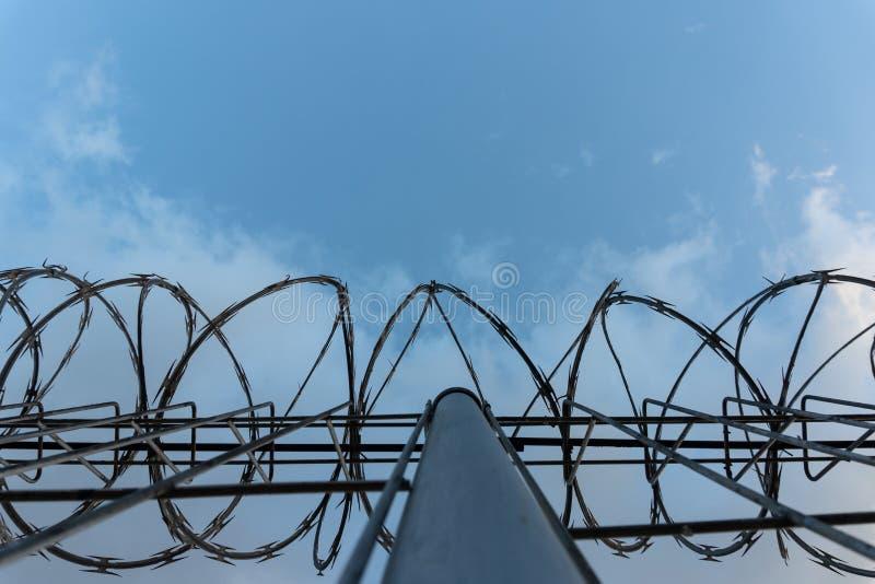 Οδοντωτός - φράκτης καλωδίων με το φωτεινό μπλε ουρανό για να αισθανθεί σιωπηλός και μόνος και να θελήσει την ελευθερία Δραματικά στοκ φωτογραφία