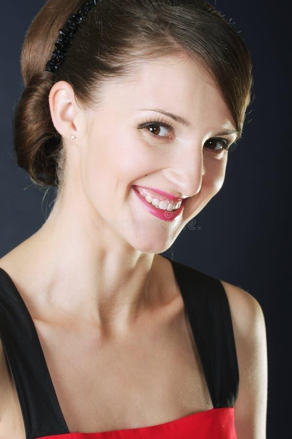 Οδοντωτό brunette χαμόγελου στο κόκκινο στοκ φωτογραφία με δικαίωμα ελεύθερης χρήσης