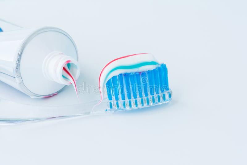 Οδοντόβουρτσα του σαφούς πλαστικού με τις μπλε σκληρές τρίχες, άσπρες μπλε κόκκινες συμπιέσεις οδοντόπαστας από έναν σωλήνα στοκ φωτογραφίες