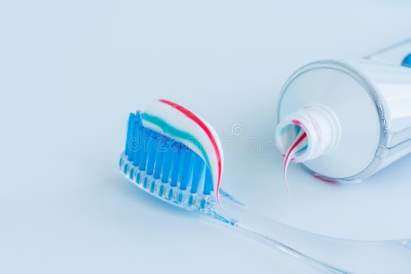 Οδοντόβουρτσα του σαφούς πλαστικού με τις μπλε σκληρές τρίχες, άσπρες μπλε κόκκινες συμπιέσεις οδοντόπαστας από έναν σωλήνα στοκ εικόνα με δικαίωμα ελεύθερης χρήσης