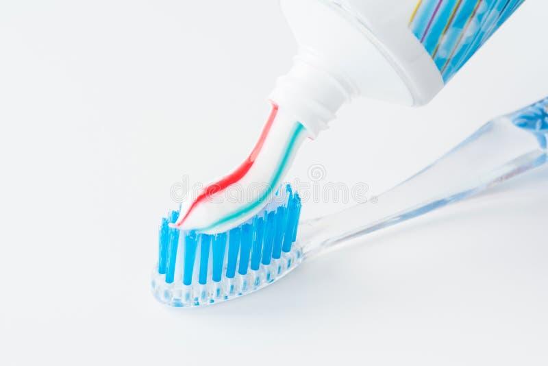 Οδοντόβουρτσα του σαφούς πλαστικού με τις μπλε σκληρές τρίχες, άσπρες μπλε κόκκινες συμπιέσεις οδοντόπαστας από έναν σωλήνα στοκ φωτογραφίες με δικαίωμα ελεύθερης χρήσης