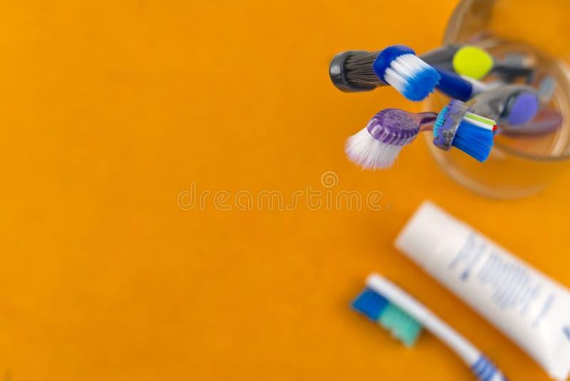 Οδοντόβουρτσες σε γυαλί σε πορτοκαλί φόντο - κοντινή όψη στοκ εικόνες